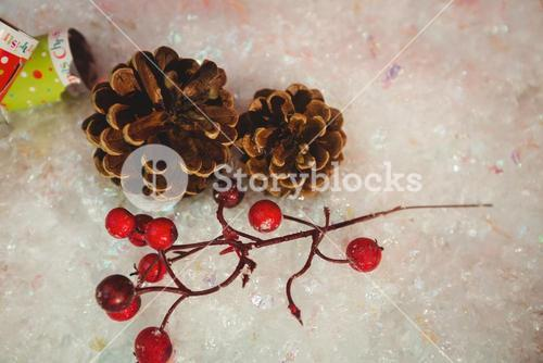 Pine cone, cherry and christmas crackers on snow