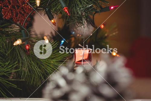 Fairy light and small gift box hanging on christmas tree