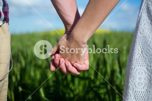 Mid section of couple holding hands in field
