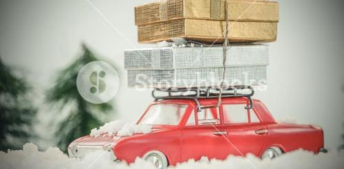 Toy car carrying christmas present on fake snow