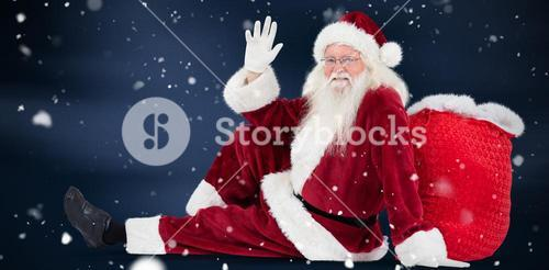 Composite image of santa sits leaned on his bag and waves
