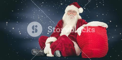 Composite image of santa sits next to his bag