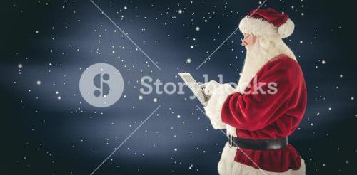 Composite image of santa uses a tablet pc