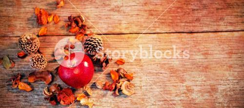 Apple and pine cone on wooden plank