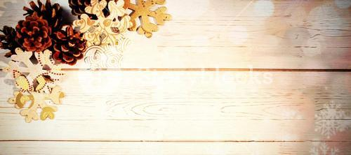 Snowflakes and pine cone on wooden plank