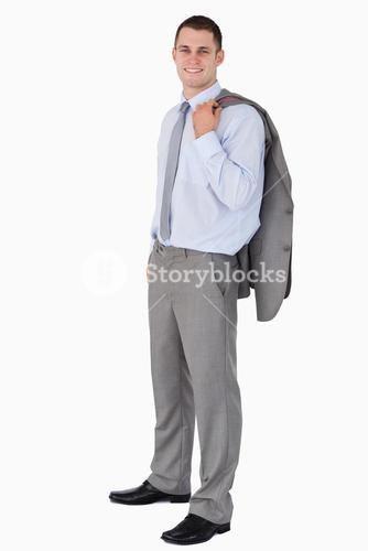 Smiling businessman with his coat tossed over his shoulder