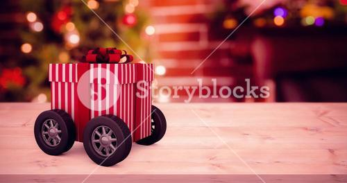 Composite image of striped white and red gift box with wheels