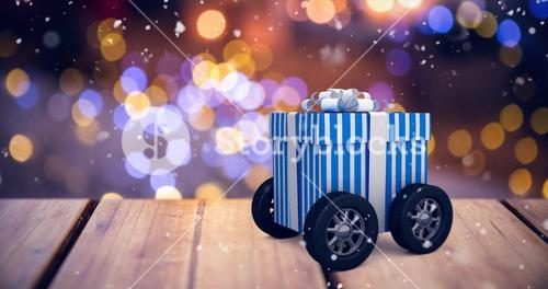 Composite image of digitally generated image of gift box with wheels