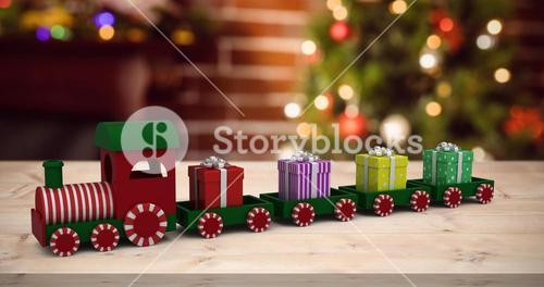 Composite image of train model carrying gift boxes