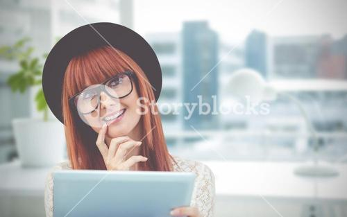 Composite image of smiling hipster woman using her tablet