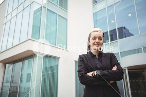 Portrait of smiling businesswoman standing with arms crossed