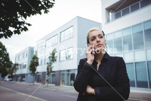 Thoughtful businesswoman standing with arms crossed