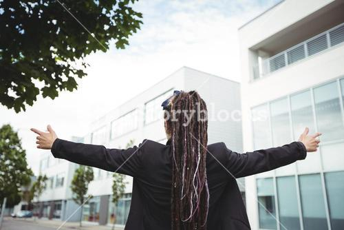 Businesswoman standing with arms outstretched