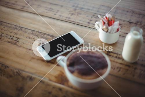 Close-up of coffee cup with mobile phone and milk bottle