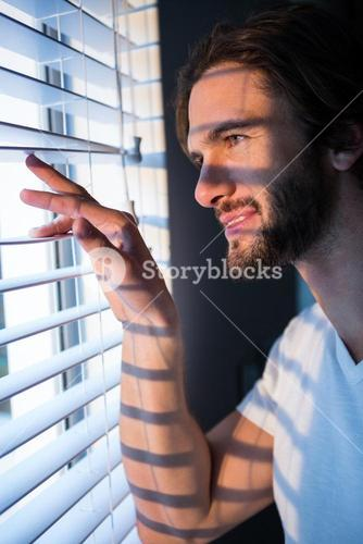 Man looking through window blinds after waking up