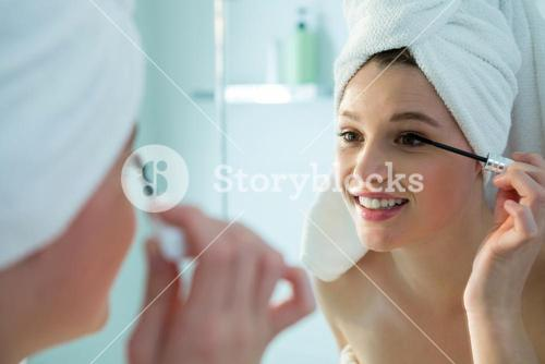Woman applying mascara on eyelashes in bathroom