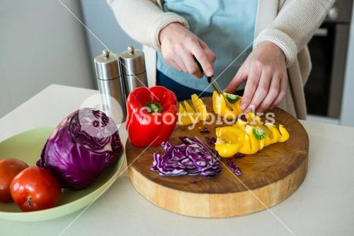 Mid section of woman cutting yellow bell pepper in kitchen