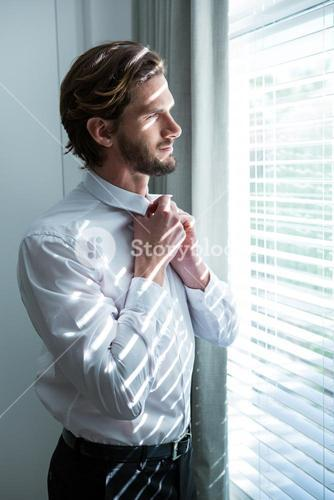 Man getting dressed while looking through window blinds