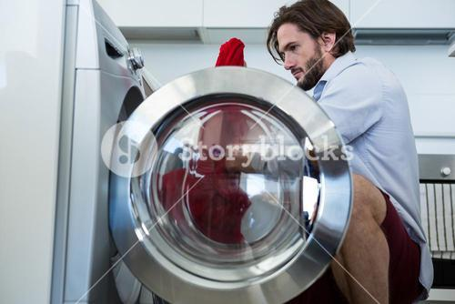 Man putting his clothes into washing machine