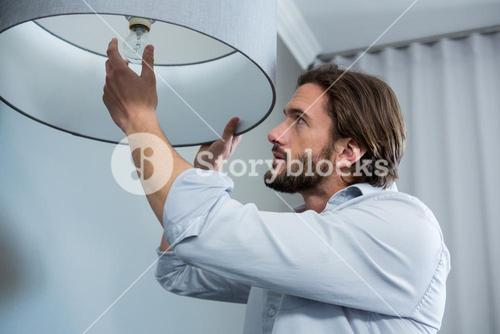 Man installing a bulb in living room