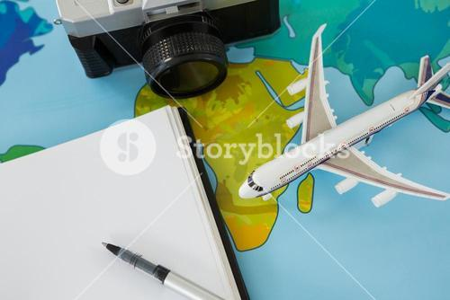Digital camera, dairy, pen, and airplane model on table
