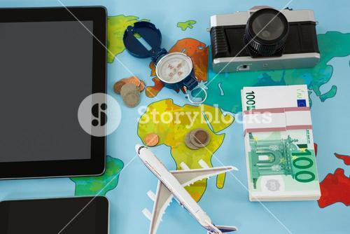 Electronic gadgets, camera, dollar, compass, and airplane model
