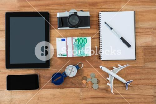 Electronic gadgets, camera, dollar, coin, diary, pen, compass, and airplane model
