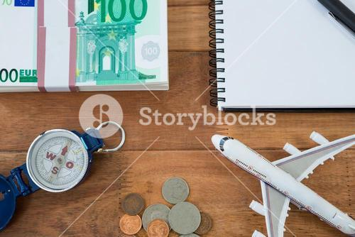 Dollar, coin, dairy, pen, compass, and airplane model