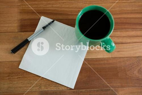 Close-up of coffee mug with blank paper and pen