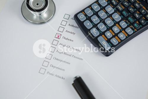 Close-up of health evaluation form with diabetes check and calculator, stethoscope