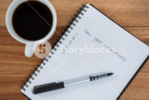 Close-up of coffee cup with diary and pen