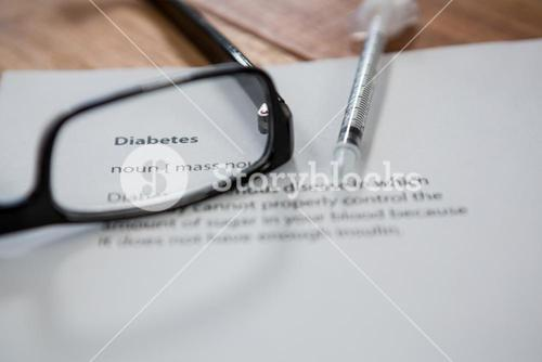 Close-up of injection with diabetes test paper and spectacle