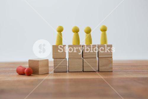 Yellow Figurines on wooden blocks in a row and red figurine fallen on ground