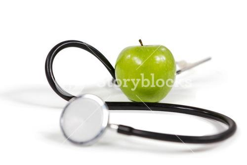 Stethoscope and apple on white background