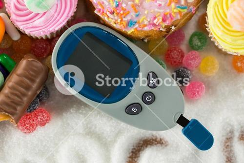 Various types of doughnuts and cupcakes with glucometer