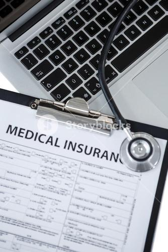 Clipboard with medical insurance paper, stethoscope and laptop