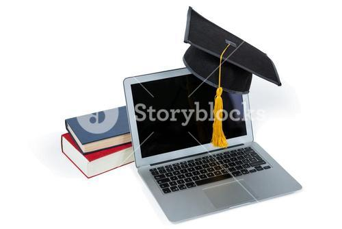 Laptop with mortarboard and books