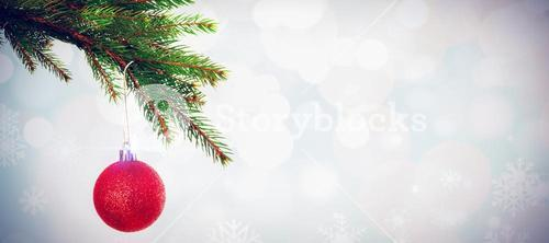 Composite image of red christmas bauble hanging from branch
