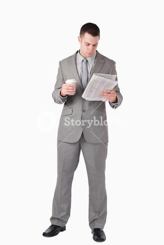 Portrait of a businessman reading the news while holding a cup of coffee
