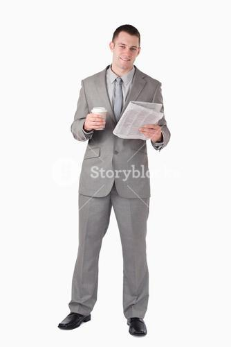 Portrait of a businessman reading the news while holding a cup of tea