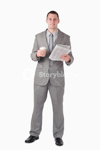 Portrait of a businessman holding a newspaper and a cup of coffee