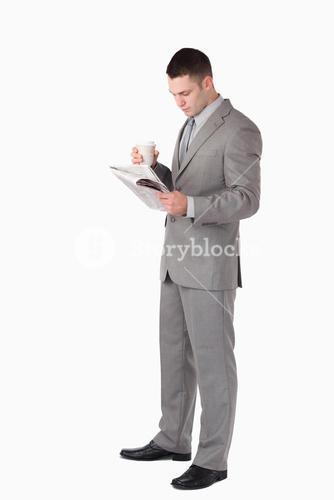 Portrait of a businessman holding a cup of tea while reading the news
