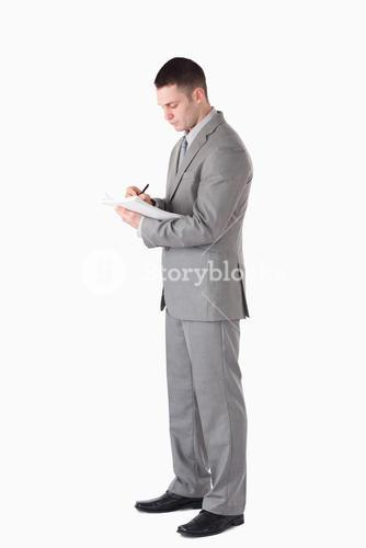 Portrait of a serious businessman taking notes