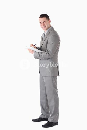 Portrait of a young businessman taking notes