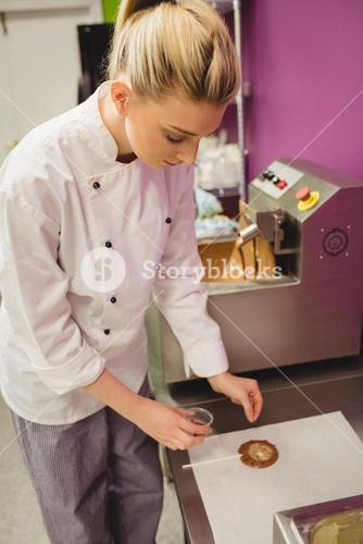 Worker preparing lollipop on wax paper