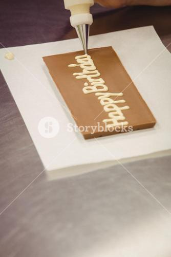 Worker writing happy birthday with piping bag on chocolate plaque