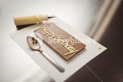 Happy birthday written on chocolate plaque