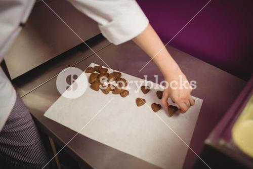 Worker arranging heart shaped chocolates on wax paper