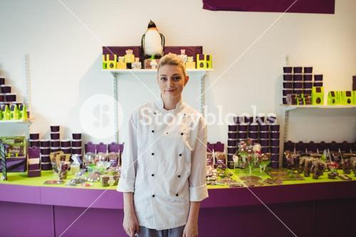 Portrait of worker standing next to chocolate display