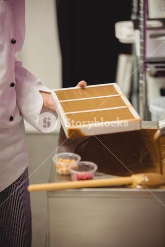 Mid section of worker holding chocolate mould